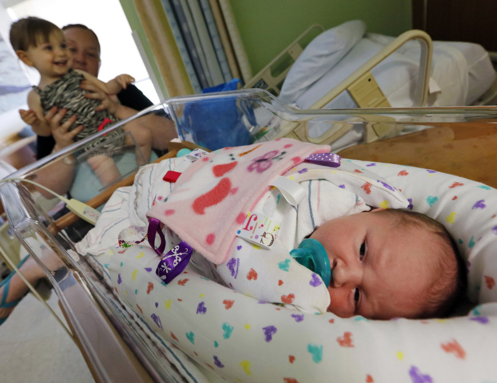 Amanda Fielding and her daughter Briella Debonise, 20 months, take a closer look at Braylin Debonise, 9 days old, at St. Luke's Hospital in New Bedford, Mass. Both of Fielding's daughters were born with an addiction to methadone.