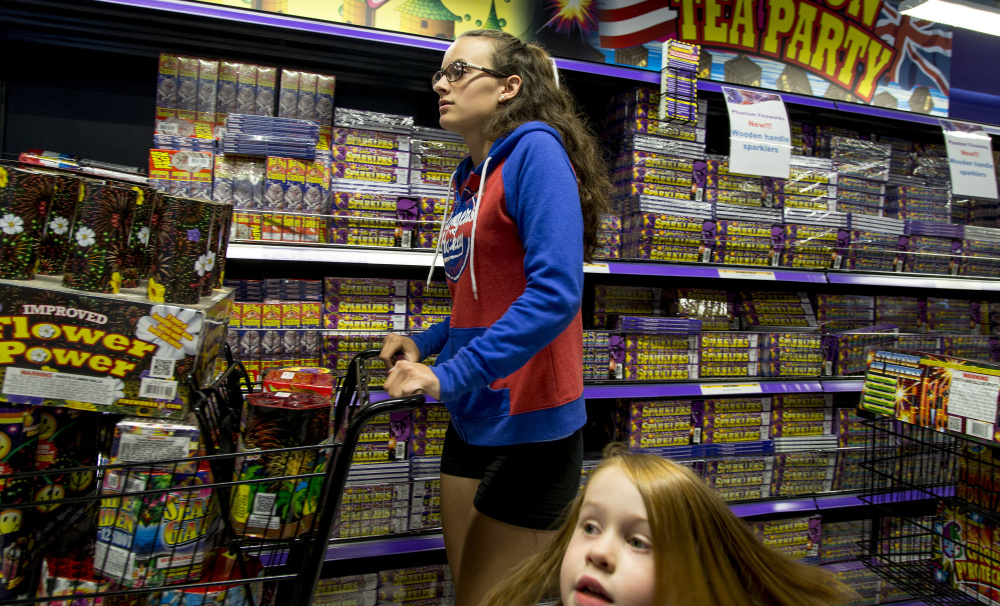 Hannah McIntyre of Bristol, Conn., pushes a shopping cart full of fireworks along an aisle in Phantom Fireworks in Scarborough on Friday while shopping with her family for an Independence Day celebration at Sebago Lake.