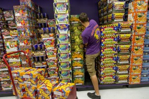 Grant Emrich restocks piles of fireworks at Phantom Fireworks in Scarborough on Friday as customers shop in preparation for Independence Day on Monday.