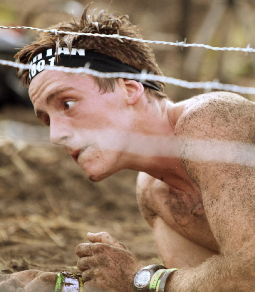 Isaac Douglass crawls under barbed wire during a Spartan race in Massachusetts in August 2015 – one of many such obstacles in the sport.