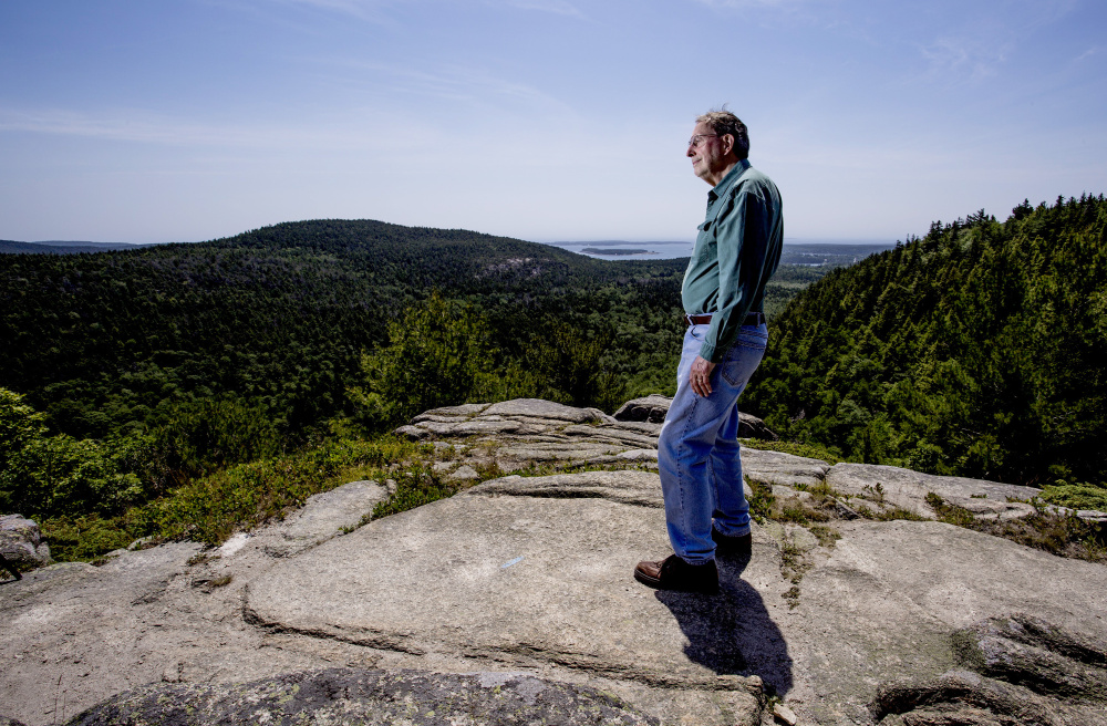 Jack Russell, a board member of Friends of Acadia and a lifelong resident of Mount Desert, poses atop Beach Cliff last week. The park inhabits many of his earliest memories, and this is where he and his wife have retired.