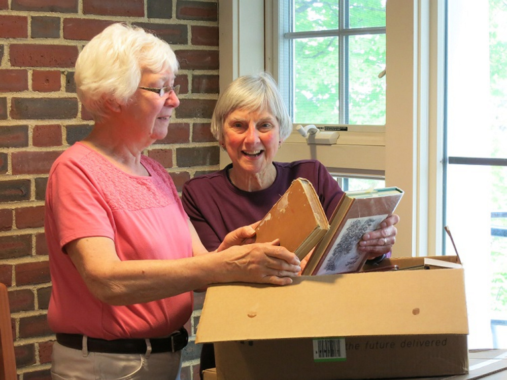 Rosalie Ketchum, left, and Ann Siekman look over books donated for the Friends of Norway Memorial Library's used book sale Thursday through Saturday.