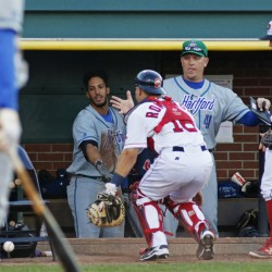 PORTLAND, ME - JULY 3: Hartford coach #41 Darin Everson is ready to catch Portland Sea Dogs catcher Jake Romanski as he chases a loose ball that tipped off his glove in the 7th inning vs. Hartford Yard Goats at Hadlock Field. Sea Dogs third baseman Sean Coyle looks on. (Photo by Jill Brady/Staff Photographer)