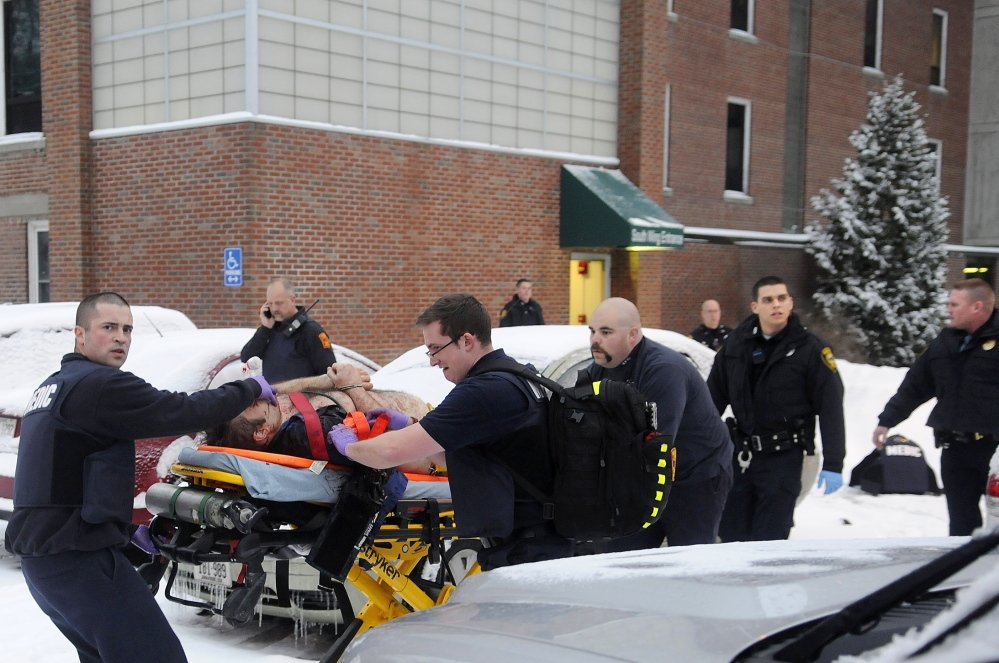 Firefighters and police, wearing protective gear, escort a man shot by an Augusta police officer on Jan. 12, 2015, following a confrontation at an office at the former MaineGeneral Medical Center in Augusta.