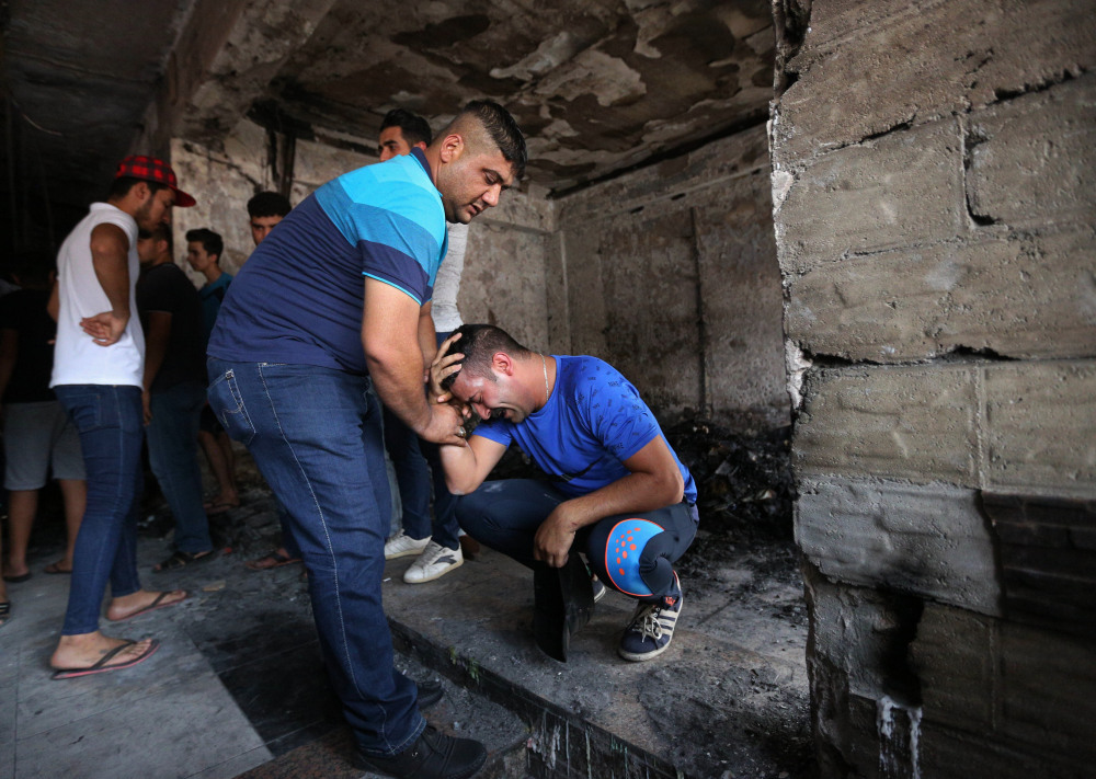 Iraqi men grieve Monday at the scene of the suicide car bombing in Baghdad. The Islamic State said it carried out the attack, according to an official of the Iraqi Interior Ministry.