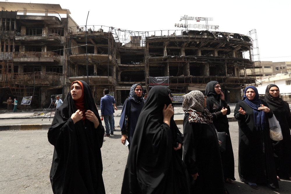 Iraqi women await word on missing family members Monday, the day after a car bomb blast in a commercial area of Baghdad killed at least 200 people.