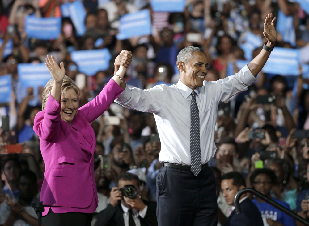 President Obama and Hillary Clinton wave to the crowd after speaking Tuesday at a campaign rally for Clinton in Charlotte, N.C., where the president said,