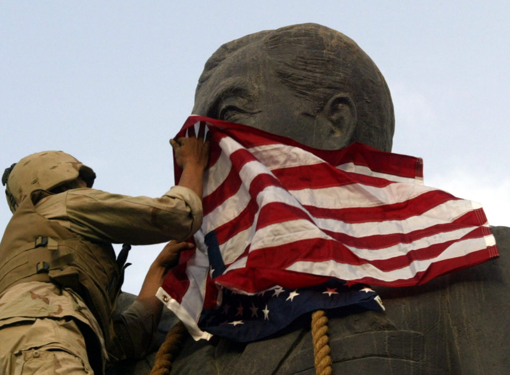 A U.S. Marine covers the face of a statue of Iraqi President Saddam Hussein – with a U.S. flag in Baghdad on April 9, 2003.