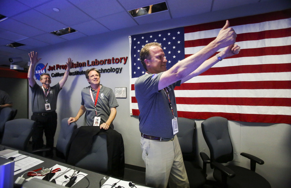 Michael Watkins, right, Scott Bolton, center, and Jim Green react in Mission Control at NASA's Jet Propulsion Laboratory as the solar-powered Juno spacecraft goes into orbit around Jupiter on Monday July 4, 2016 in Pasadena, Calif. (AP Photo/Ringo H.W. Chiu, Pool)