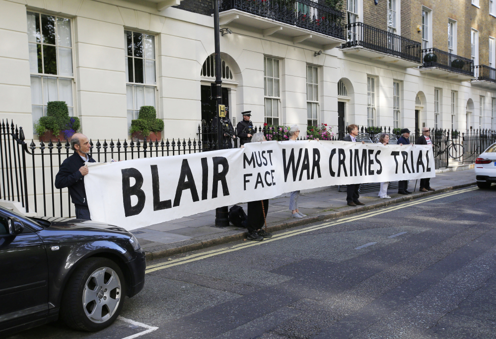 Protesters hold a banner outside the home of former Prime Minister Tony Blair ahead of the publication of the report into the Iraq War in London on Wednesday.