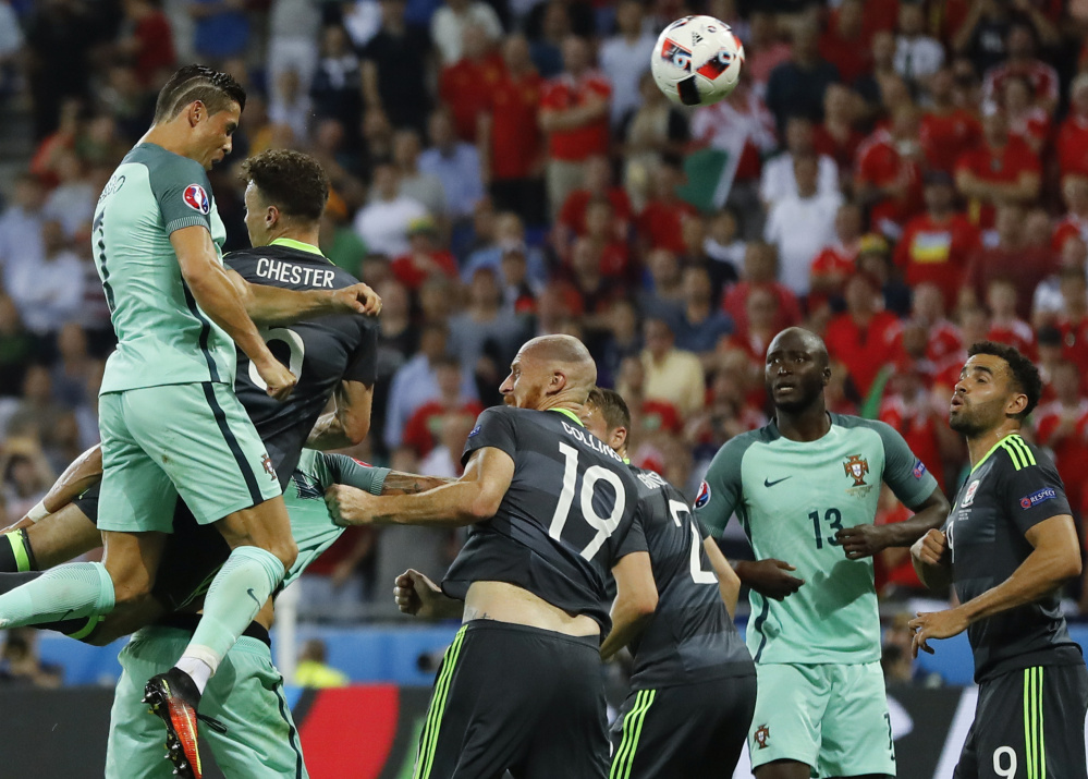 Cristiano Ronaldo, left, leaps over the defense to score on a header Wednesday – the first goal in a 2-0 victory for Portugal against Wales in the European Championship semifinals at Lyon, France.