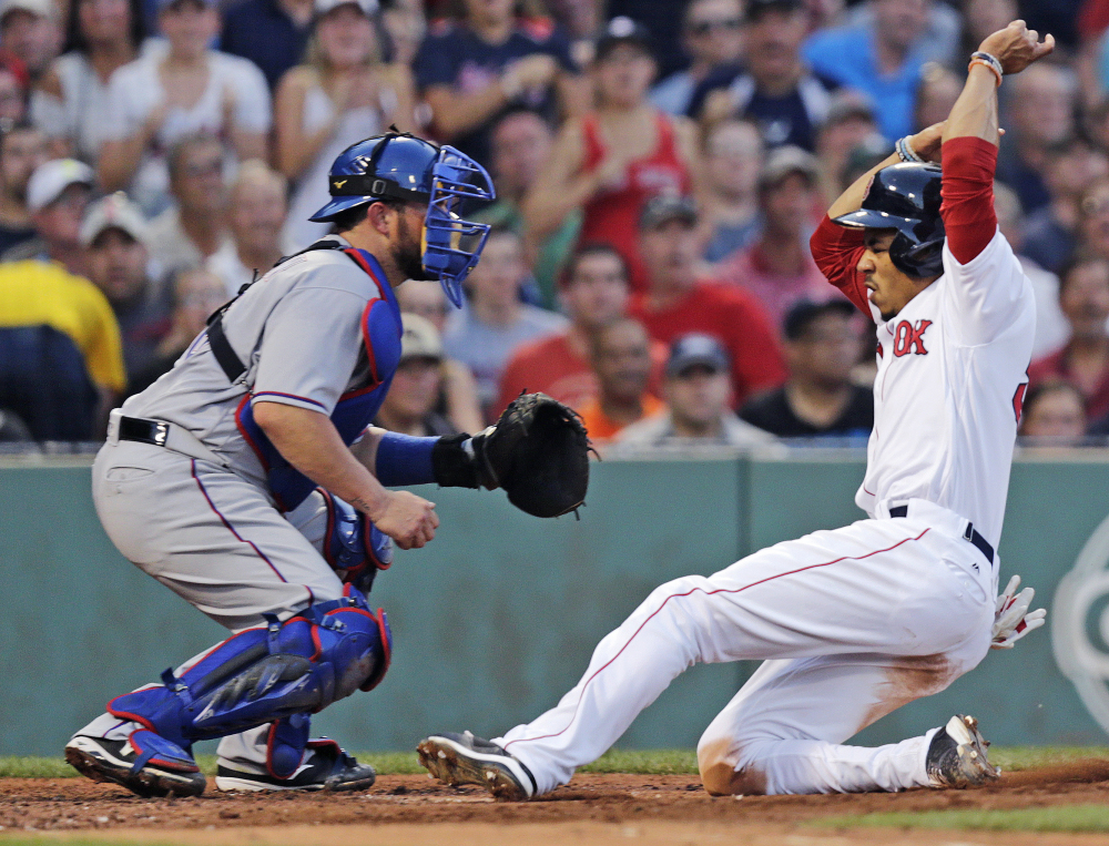 Mookie Betts beats the throw and slides home safely on a sacrifice fly by David Ortiz in the second inning. Boston blew the game open with five runs in the second.