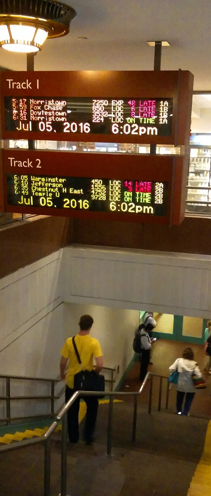 Passengers walk beneath train schedule displays listing delays as they head to boarding platforms for regional commuter trains operated by Philadelphia's main transit agency Tuesday.