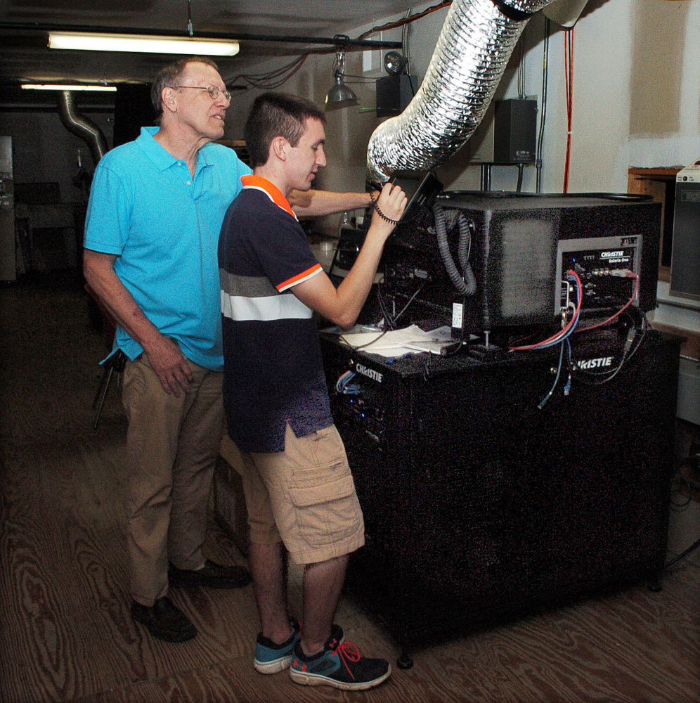 Railroad Square Cinema co-owner Alan Sanborn, left, watches on Wednesday as Logan Rollins sets up a digital projector for the Maine International Film Festival, which begins Friday night.