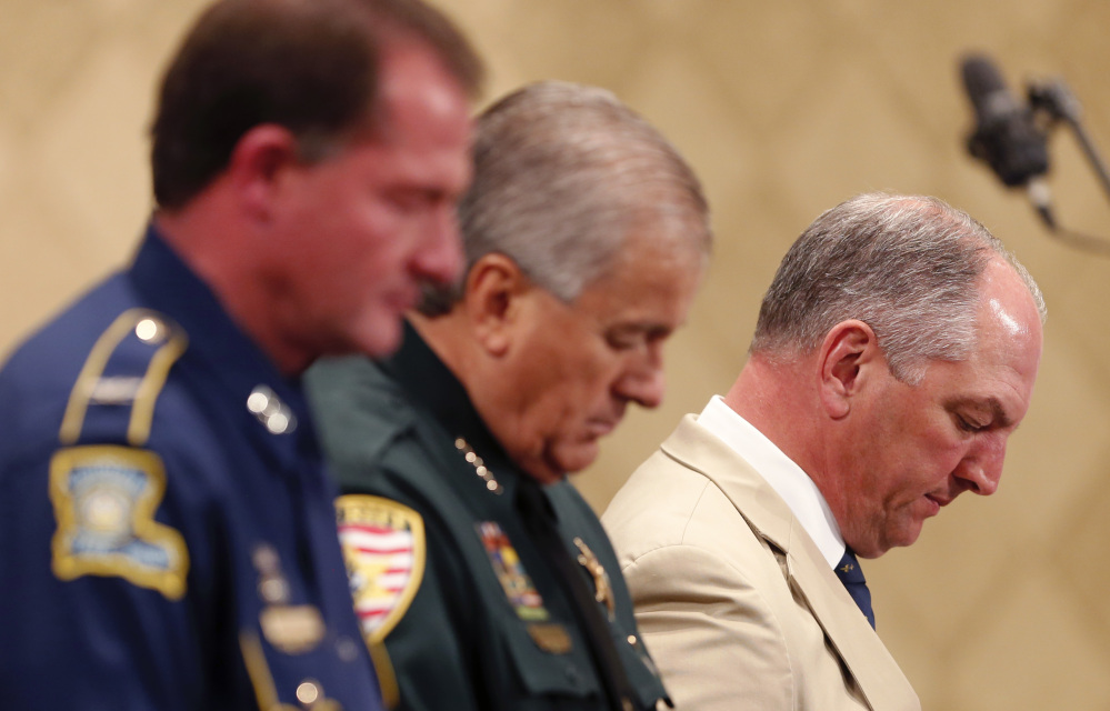 Louisiana Gov. John Bel Edwards, far right, bows his head in prayer with Baton Rouge Sheriff Sid J. Gautreaux III and Louisiana State Police Superintendent Colonel Michael D. Edmonson, left, at a prayer vigil Thursday for Alton Sterling, who was shot by Baton Rouge police on Tuesday.