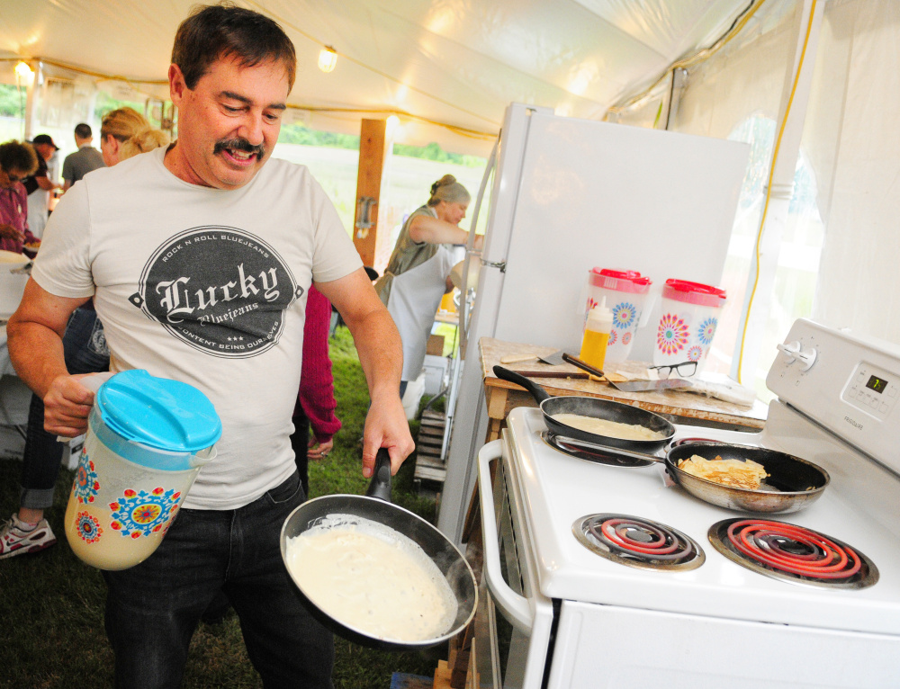 Larry Fleury swirls batter around in a pan Friday as he makes crepes during the opening night of Le Festival de La Bastille in Augusta.