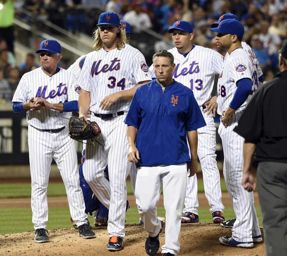 Mets Manager Terry Collins, left, looks to the dugout as a trainer escorts injured starting pitcher Noah Syndergaard from the mound Friday night.