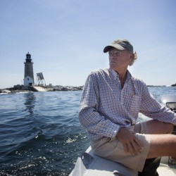 """Ford Reiche, who has been painstakingly restoring Halfway Rock Lighthouse since acquiring it two years ago, motors out to a larger vessel as he departs from """"the Rock"""" on Wednesday. Access to the remote Casco Bay beacon is always difficult and sometimes impossible."""