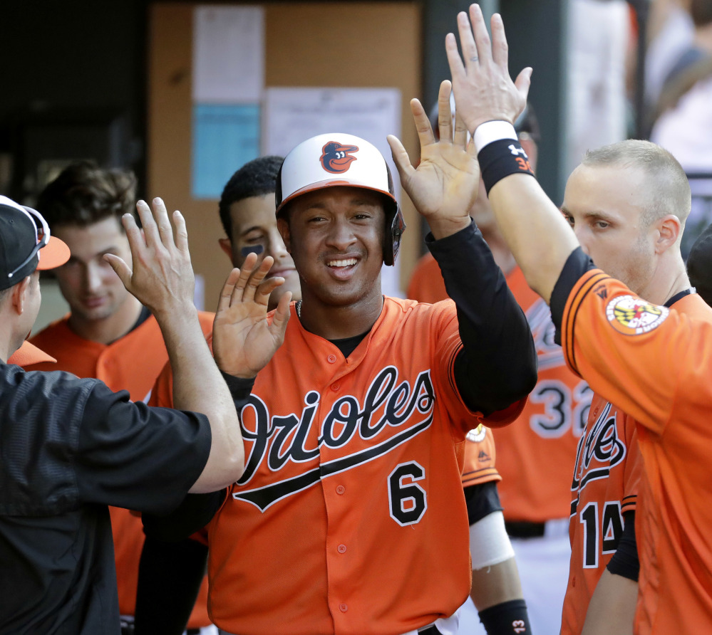 Baltimore's Jonathan Schoop high-fives teammates after scoring on a balk by Los Angeles Angels reliever Joe Smith in the seventh inning of Saturday's victory.