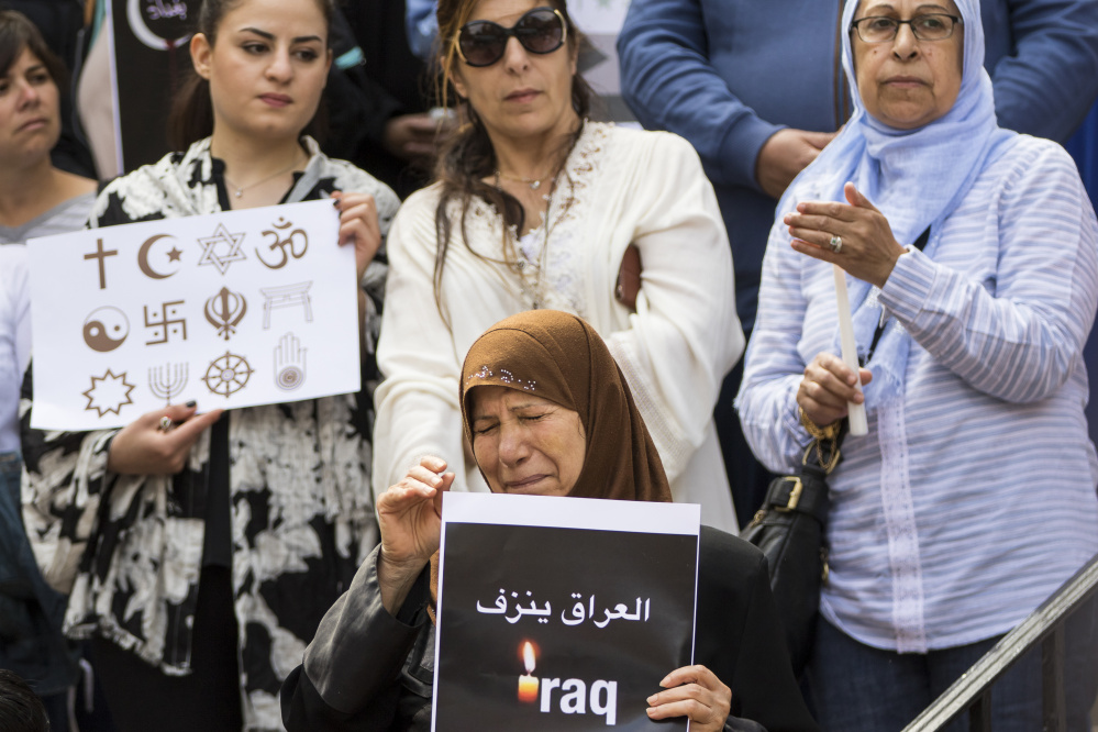 Hamdiyah Alwakeal, center, breaks down in tears during the vigil. Alwakeal says her 17-year-old nephew, Ali Alwakeal, was killed in the attack.