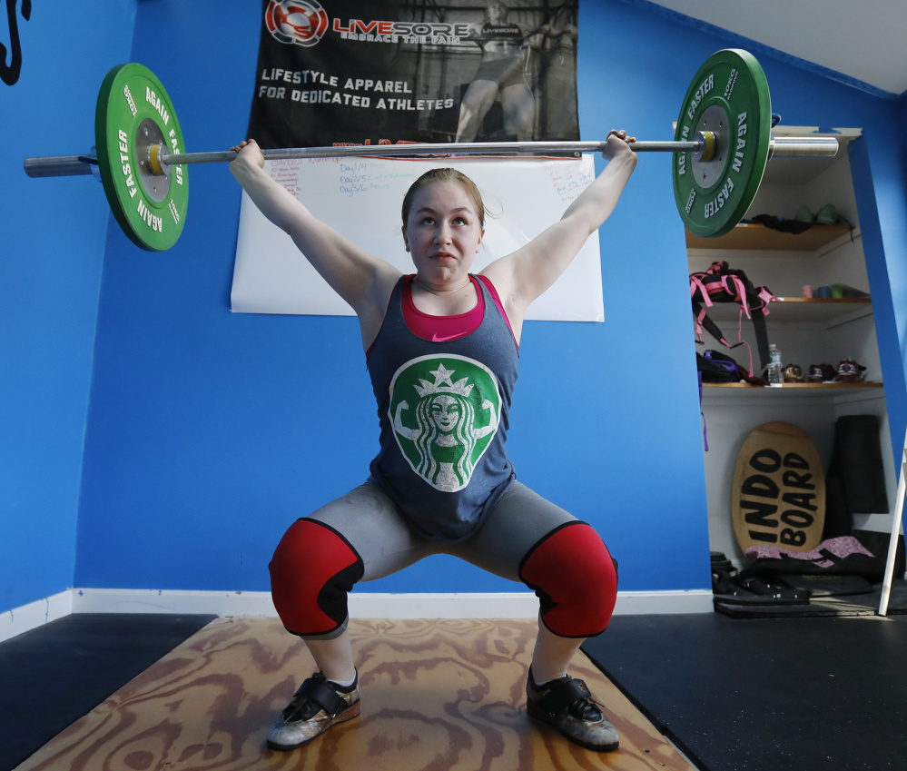 Emily McNally, 16, works out at her home gym. At the USA youth weightlifting competition last month in Texas, she finished third among 20 competitors in her age and weight class while setting three New England records.
