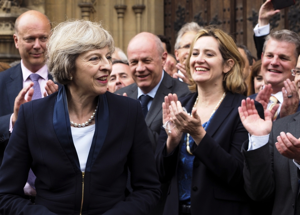 Britain Home Secretary Theresa May, left, is applauded by Conservative Party members of Parliament outside the Houses of Parliament in London on Monday.