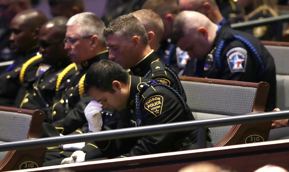 Law enforcement officers bow their heads in prayer during funeral services for Dallas Police Sr. Cpl. Lorne Ahrens at Prestonwood Baptist Church in Plano, Texas, on Wednesday.