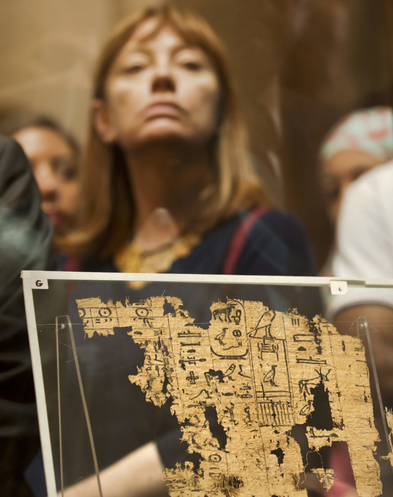 A visitor looks at one of the oldest papyruses among the collection of King Khufu.