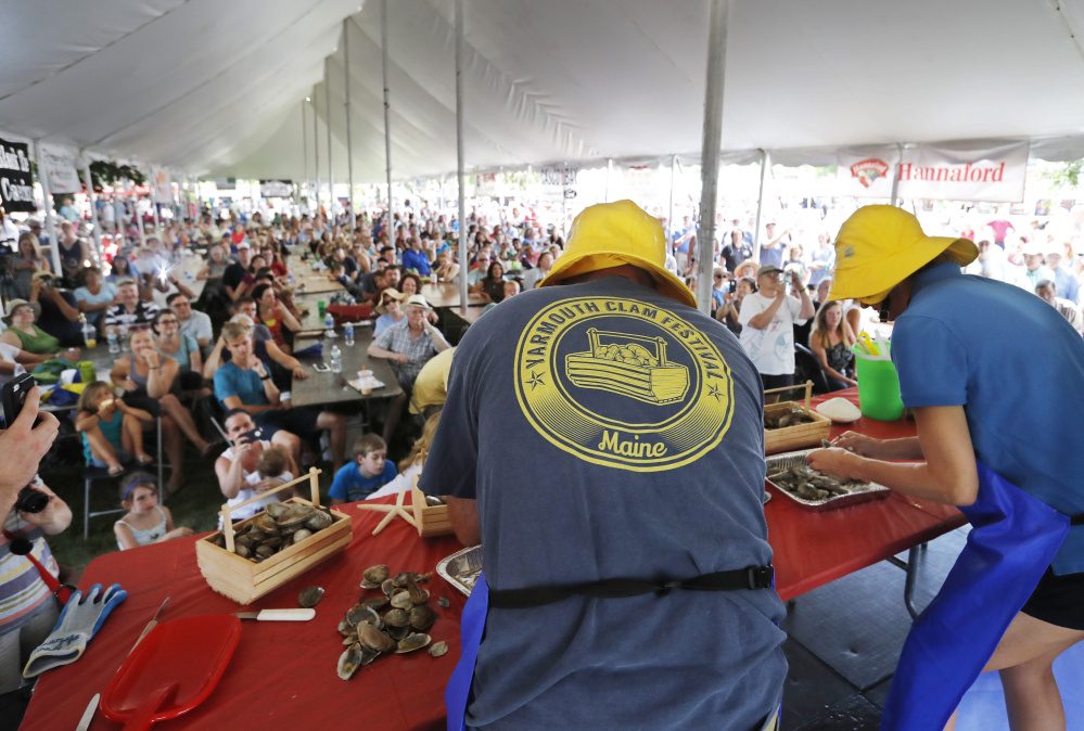 A crowded tent of spectators watch the Maine State Clam Shucking Contest Saturday, July 16, 2016 at the Yarmouth Clam Festival in Yarmouth, Maine. (Photo by Joel Page/Staff Photographer)