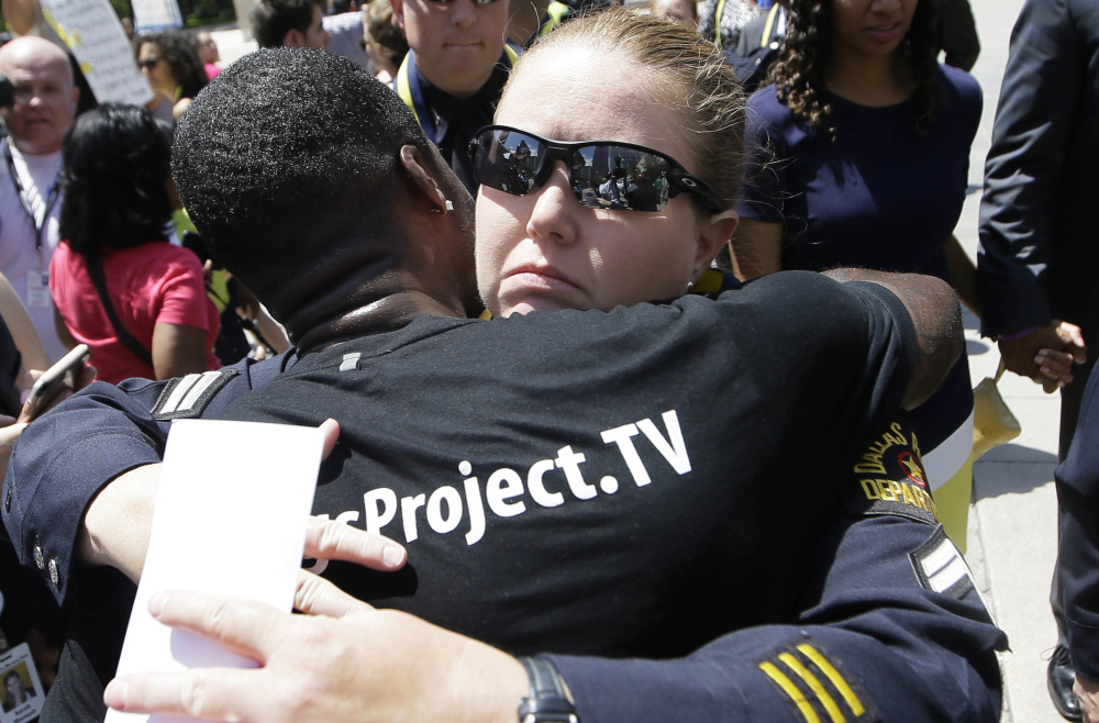 A Dallas police officer is hugged after a memorial service for fallen fellow officers Tuesday, in which President Obama declared that a week of deeply troubling violence has seemed to expose