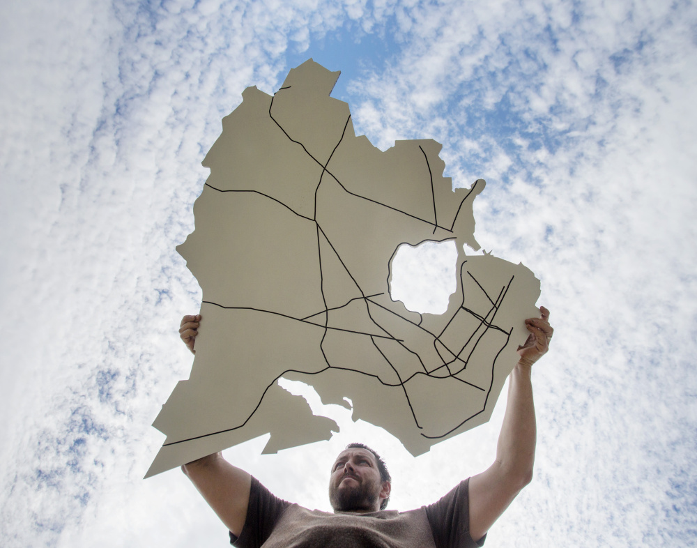 Jake Ryan of Open Bench Project holds art in the shape of Portland, jagged coastline, Back Cove and all, that will be used to help the public provide ideas for the city's master  plan.