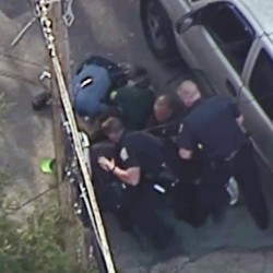 This image made from a helicopter video shows officers pummeling Richard Simone, who had kneeled on the ground after a high-speed chase May 11 in Nashua, N.H.