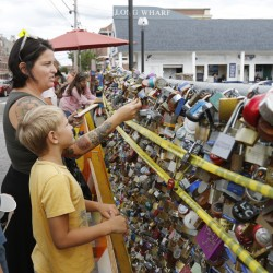 Kelly Wright, joined by sons Colby, 12, and Tanner, 8, attaches a padlock to the Love Locks fence Tuesday on Portland's Commercial Street. Deemed a public safety risk, the fence will be removed within two weeks.