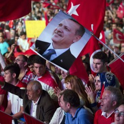 """Government supporters wave Turkish flags and hold a picture of Turkish President Recep Tayyip Erdogan during a rally in Taksim Square in Istanbul on Tuesday. The Turkish government accelerated its crackdown on alleged plotters of the failed coup against Erdogan and he called the attempted putsch """"a gift from God."""" Associated Press/Petros Giannakouris"""