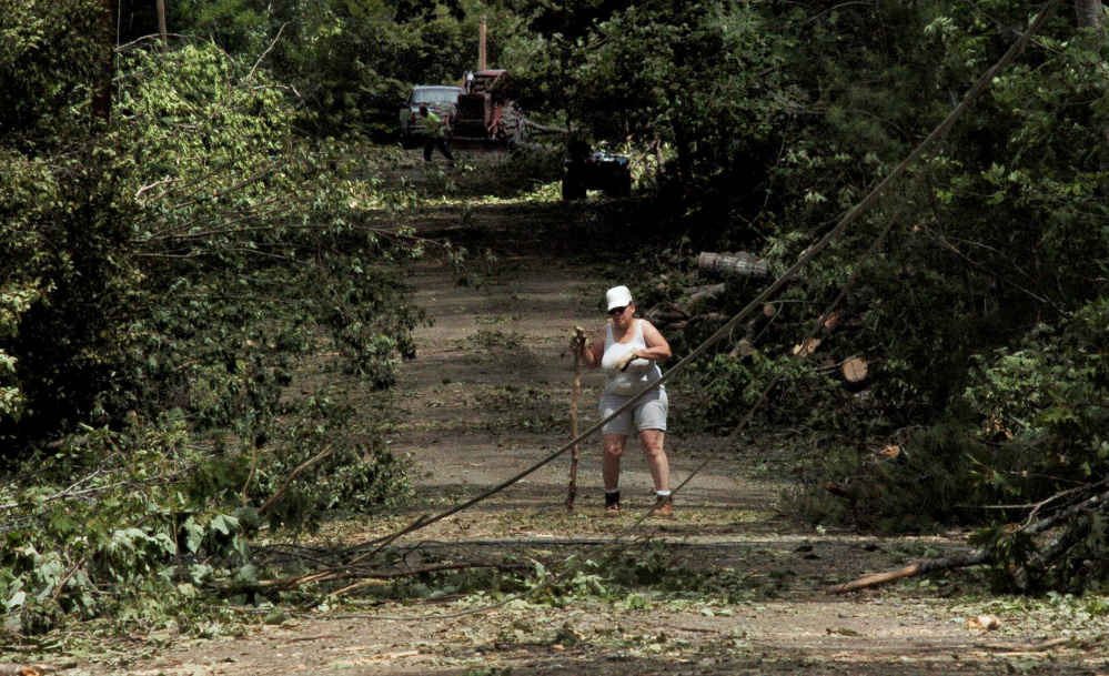 Ballard Road resident Luanne Paquin works to clear brush around utility wires and broken poles on the closed road in St. Albans on Tuesday. The road was filled with fallen trees, wires and utility poles following a severe storm Monday. A skidder machine and operator in background clear trees from the roadway.