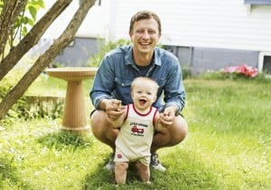Tristan Noyes, newly appointed executive director for the Maine Grain Alliance, with his son, Bentley, 7 months, in their South Portland yard.