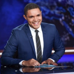 """Trevor Noah at his """"Daily Show"""" desk in New York. Observers say Noah is mixing comedy and opinion more lately than when he took over from Jon Stewart last year."""