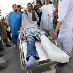 Afghans help an injured man after an explosion struck a protest in Kabul on Saturday.