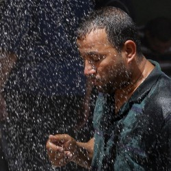 An Iraqi man cools off under an open-air shower in Baghdad on Saturday. Iraqis are enduring the year's hottest temperatures in the southern part of the country, compounded by electricity outages.