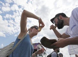 Above, Sarah McCann and Matt Elliott eat oysters from BP's Shuck Shack. At left, C.J. Elliott of West Gardiner has pretzels ready while sampling the Pilot IPA from Industrial Arts Brewing Co. of Rockland, N.Y.