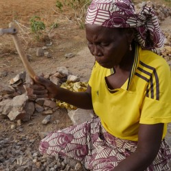 A woman crushes rocks in a quarry at Maroua, Cameroon. Menaced by hunger and suicide bombers, women spend grueling days breaking rocks into gravel to earn a living.