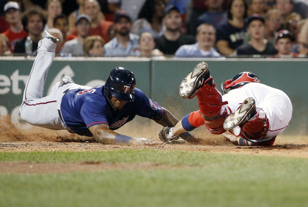 Boston catcher Sandy Leon, right, dives in an attempt to tag Minnesota's Kennys Vargas at home plate during the seventh inning of Saturday's game in Boston. Vargas was initially ruled out, but Minnesota challenged the call and it was reversed.