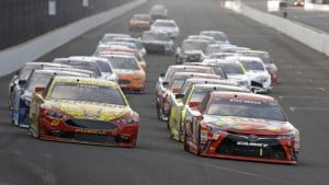 Kyle Busch, right, leads Joey Logano, left, and the rest of the field Sunday on the final restart of the Brickyard 400 at Indianapolis Motor Speedway. Busch led 149 of 170 laps as he became the first driver to sweep the Xfinity Series and Sprint Cup poles and races on the same weekend.