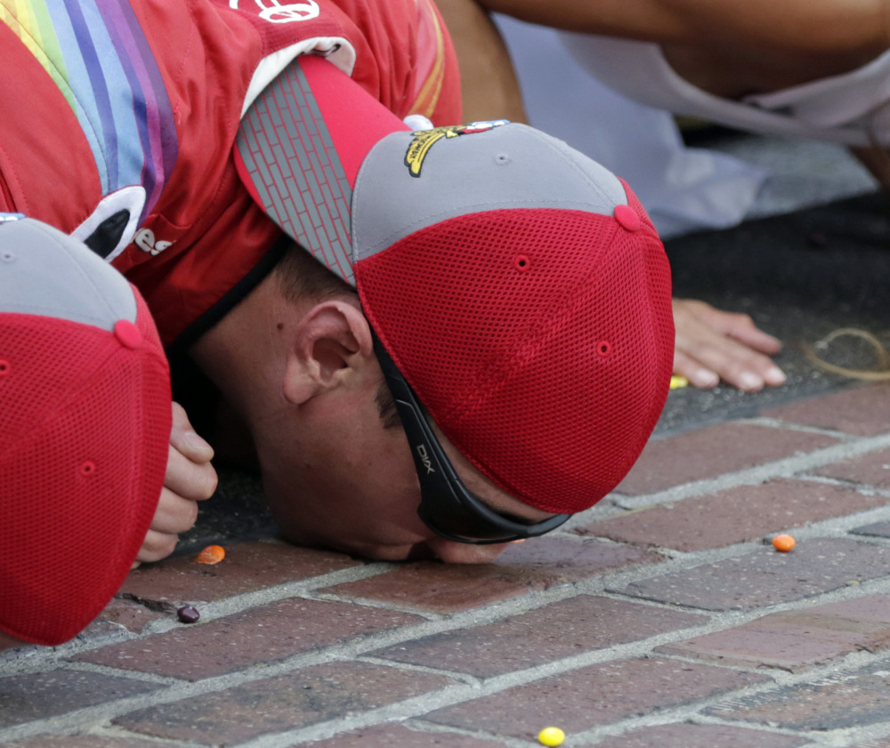 Kyle Busch kisses the yard of bricks at Indianapolis Motor Speedway after a dominant performance Sunday.