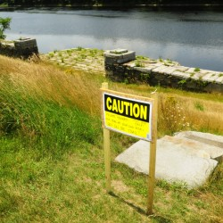 A sign tells people to stay on the Greenway Trail that has an easement across the Kennebec Arsenal property in Augusta.