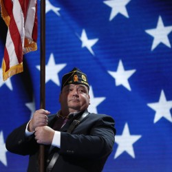 A man holds a flag on stage during a rehearsal for the singing of the National Anthem before the 2016 Democratic National Convention in Philadelphia on Monday.