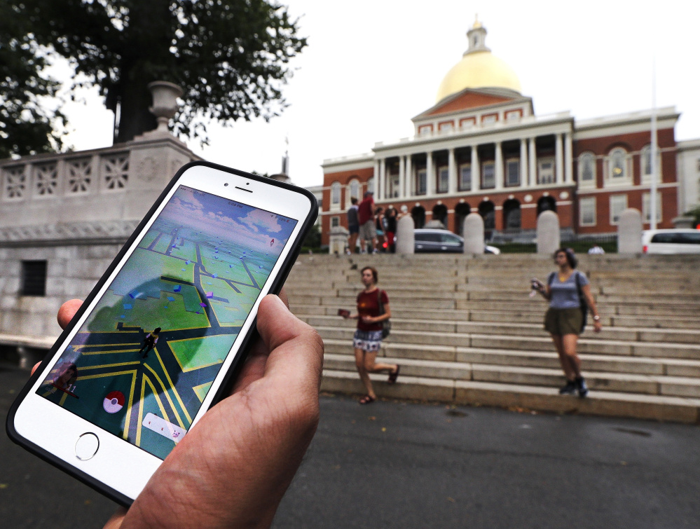 """A """"Pokemon Go"""" player looks at his mobile phone while walking through Boston Common outside the Massachusetts Statehouse. The founder of the volunteer-based historical markers website that licensed its data to game-maker Niantic Labs five years ago said he hopes enough people take their eyes off the Pokemon they're trying to catch to read the history on the markers."""
