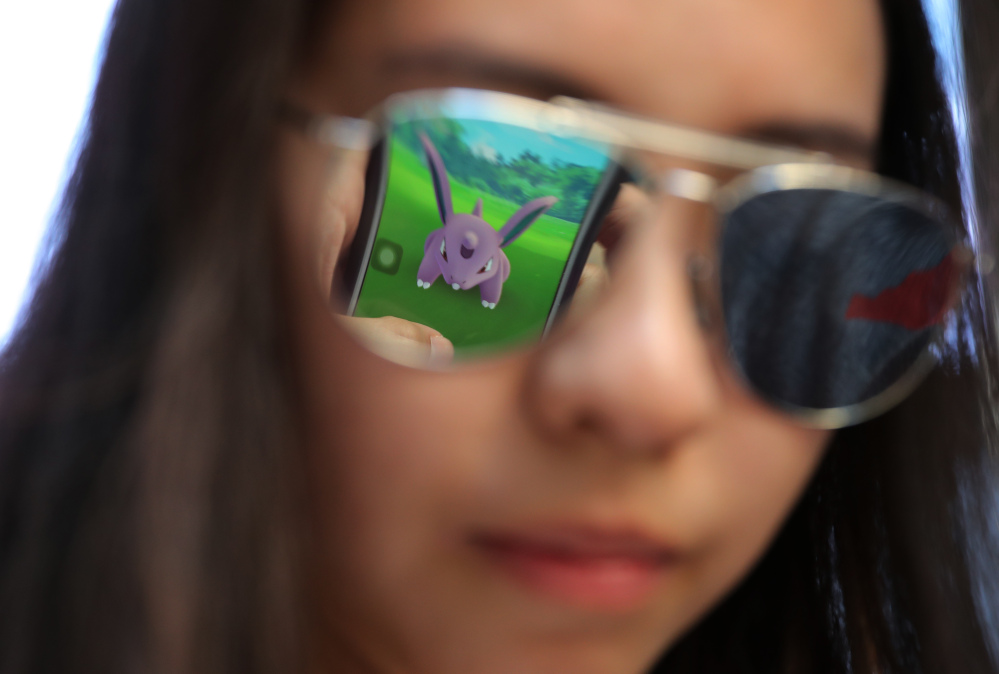 A mobile screen is reflected on a fan's sunglasses as she plays Pokemon Go in Hong Kong on Monday.