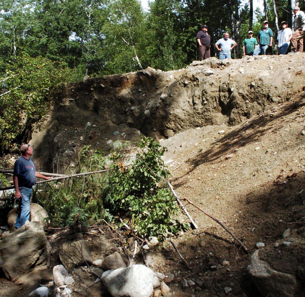 Russ Flagg, left, a landowner and board member of Mile 10 Owners Road Association looks up to a delegation of other landowners and officials on top of the washed-out Old Spencer Road in Upper Enchanted Township. The group surveyed the storm damage made last month in the area and looked at ways to fix roads that were washed out in a June storm.