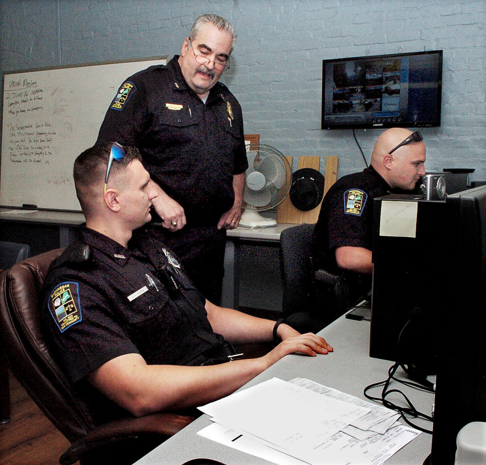 Skowhegan police Chief Don Bolduc, center, oversees officers C.J. Vera, left, and Ian Shalit filling out police reports in June. Skowhegan officers defused a situation Monday in which deadly force was